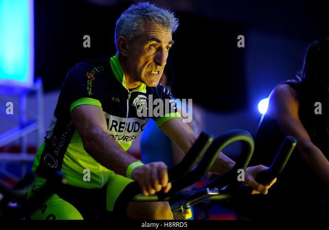Mann reitet Fahrradergometer bei einem Spinning-Kurs in der Turnhalle Stockbild