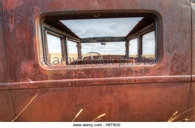 Hintere Ansicht Perspektive der ein Oldtimer links in ein Feld verrotten. Stockbild