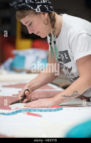 Junge tätowierte Schneiderin ein Muster ausschneiden Stockbild