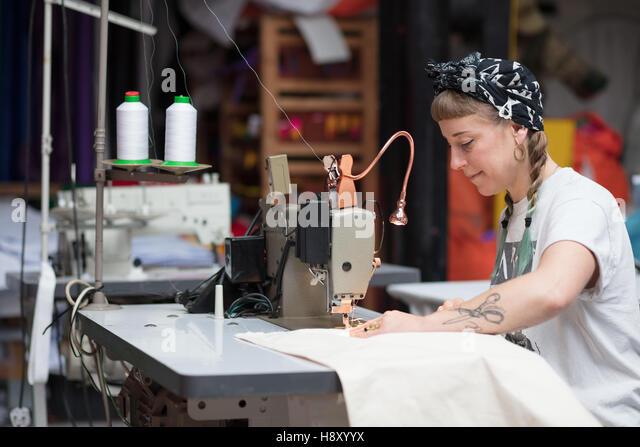 Junge tätowierte Schneiderin Nähen in einer Fabrikumgebung Stockbild