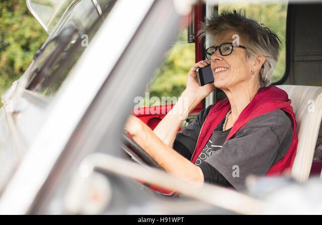 Ältere Kfz-Mechaniker einen Anruf tätigen Stockbild