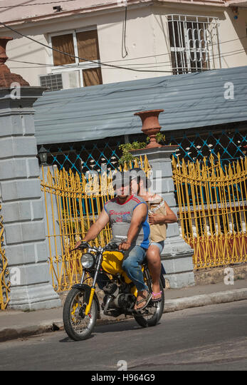Zwei gewöhnliche Kubaner auf einem Motorrad vor gelben Geländer in einer Stadt mitten in Kuba Stockbild