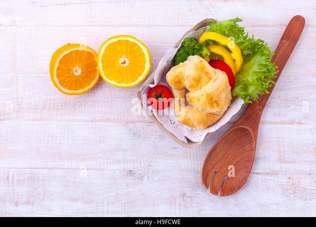 Saubere Lebensmittel Frühstück Croissant und Salat auf Holztisch. Stockbild