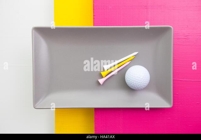 Graue Keramik Teller mit Golf-Ausrüstungen auf über weiß, gelb und rosa Holztisch, Rechteck Schale Stockbild