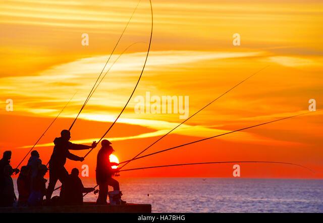 Gruppe von Fischer auf einem Pier bei Sonnenuntergang. Porto, Portugal Stockbild