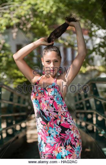 Nettes Mädchen mit lockigen Haare Kleid tragen und einen Pferdeschwanz zu machen Stockbild