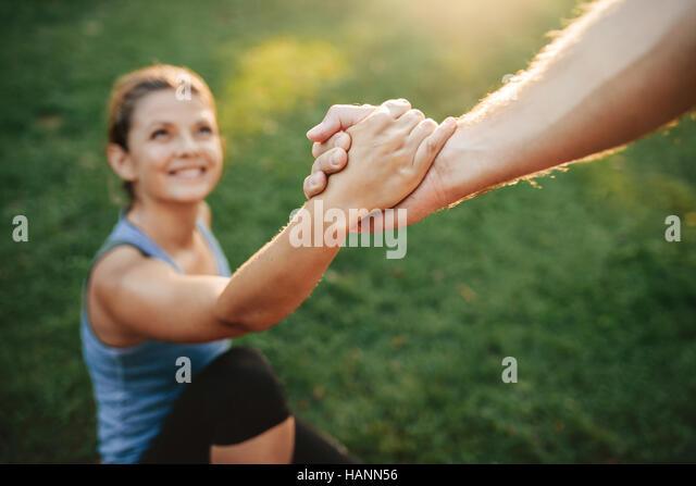 Schuss der Mann hilft Frau aufzustehen hautnah. Fokus auf den Händen der paar im Park trainieren. Stockbild