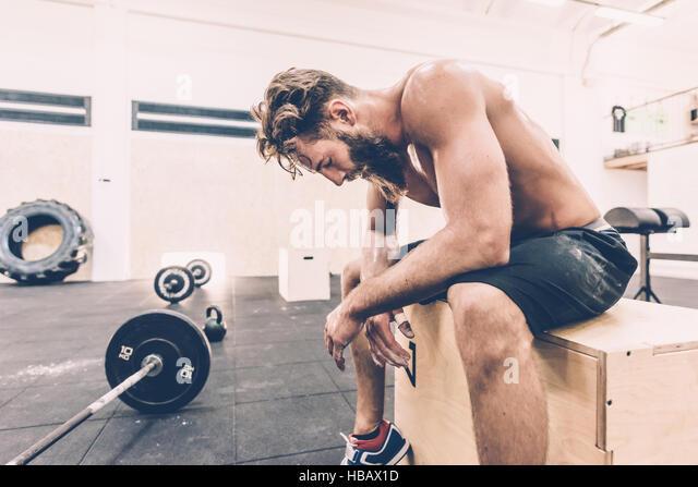 Erschöpfte männliche Cross-Trainer eine Pause von Gewichtheben im Fitness-Studio Stockbild