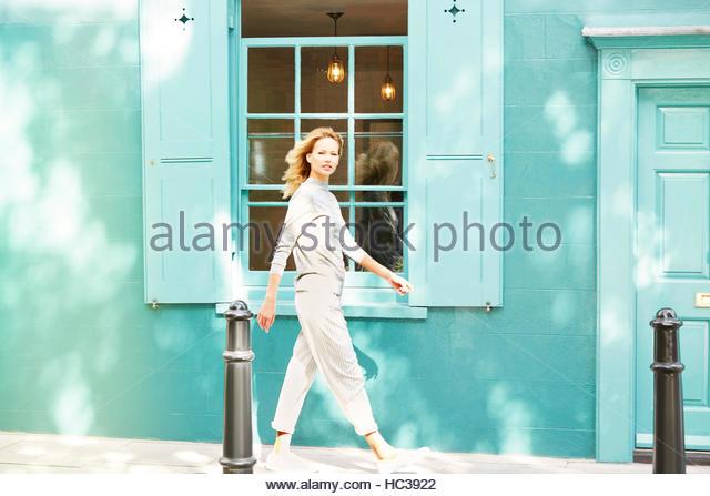 Junge Frau Bürgersteig entlang. Stockbild