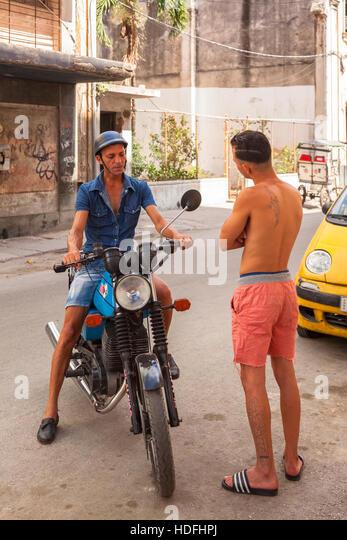 Zwei Männer (Kubaner) Gespräch auf der Straße, sitzt man auf einem Motorrad in Zentral-Havanna, Kuba. Stockbild