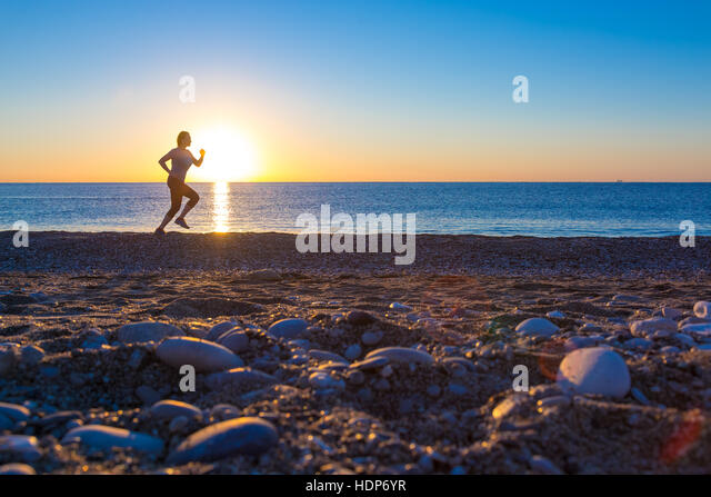 Silhouette der Sportlerin am Ocean Beach bei Sonnenaufgang Stockbild