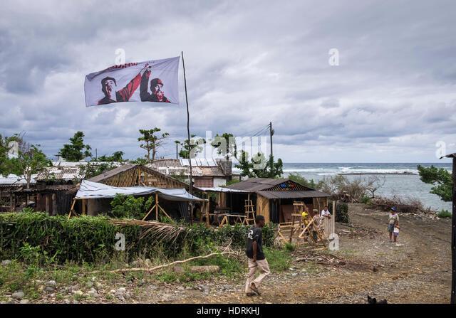 Fahne mit Fidel und Raul Castro fliegen über dem Gebiet betroffen Hurrikan Mathew Procliaiming, Venceremos, Stockbild