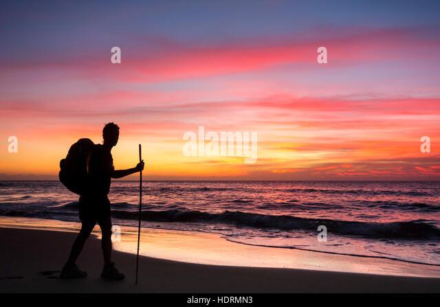 Wanderer auf abgelegenen Guigui (oder Guyguy) Strand an der West Küste von Gran Canaria bei Sonnenuntergang Stockbild