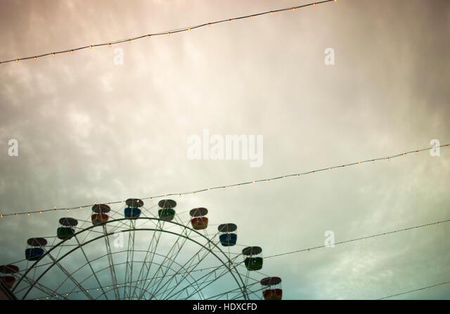 Ein Riesenrad und Drähte in einem wolkigen Himmel Stockbild