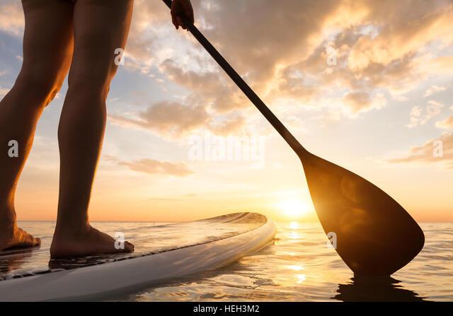 Paddle boarding auf einem ruhigen See mit warmen Sommerfarben Sonnenuntergang, Nahaufnahme Beine aufstehen Stockbild