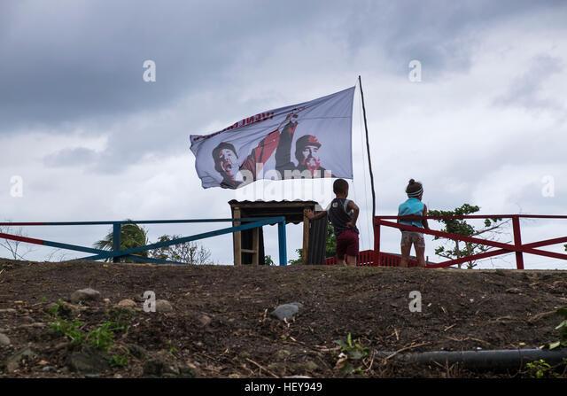 Kinder und eine Fahne mit Fidel und Raul Castro fliegen bei Yomuri, Baracoa, Schauplatz der Hilfsmaßnahmen, Stockbild
