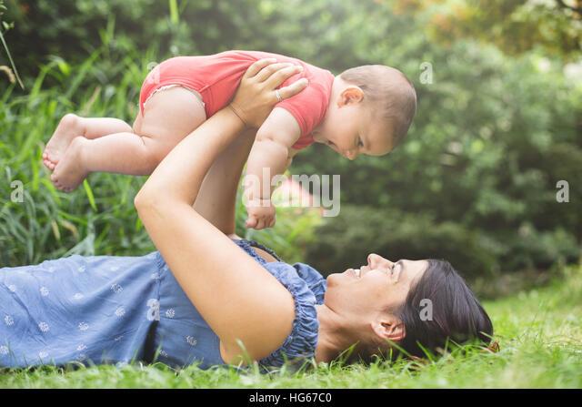 Mutter mit ihrem Baby Sohn auf dem Rasen kleben Stockbild