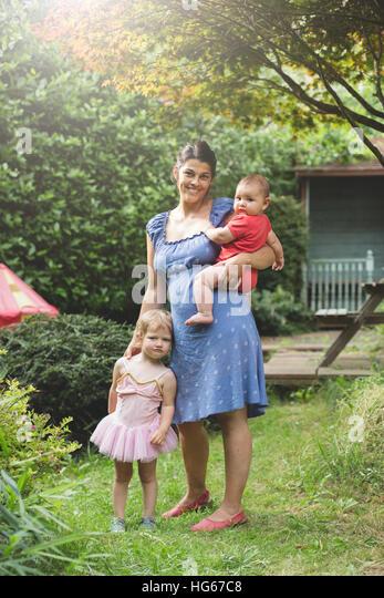 Mutter und Kinder zusammen im Garten hinter dem Haus Stockbild