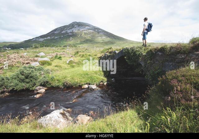 Einsamer Wanderer Stand auf einer alten Brücke in der vergifteten Glen mit Blick auf Mount Errigal. Glenveagh Stockbild