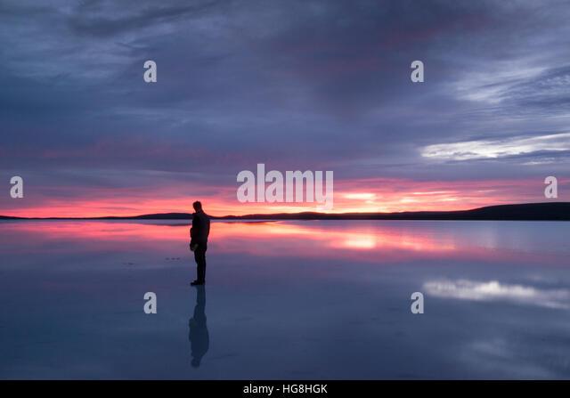 Eine Silhouette eines Mannes steht auf einem reflektierenden See bei Sonnenauf- oder Sonnenuntergang. Stockbild