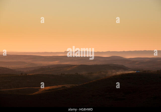 Ein Auto fährt auf einem Bergrücken in der Ferne während des Sonnenuntergangs Stockbild
