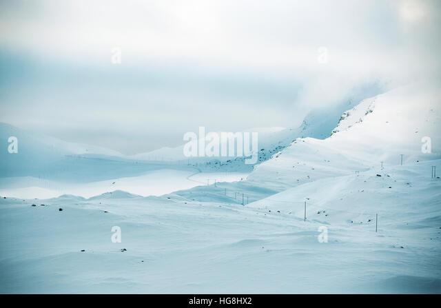 Eine Straße führt durch schneebedeckte Berge mit stürmischen Wolken in Norwegen. Stockbild