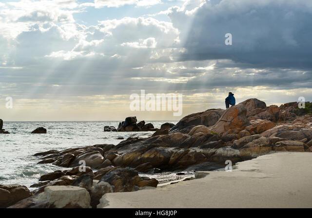 Ein Mann sitzt auf den Felsen an einem Strand, Blick auf den Ozean mit Göttern Strahlen Sonnenlicht durch Wolken Stockbild