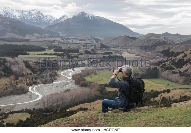 Reisende mit Rucksack und Fernglas liegt am Hügel. Stockbild
