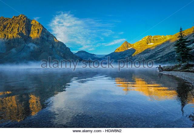 Ein Fotograf bewundert Reflexionen von Crowfoot Mountain und Mount Thompson in Bow Lake. Stockbild