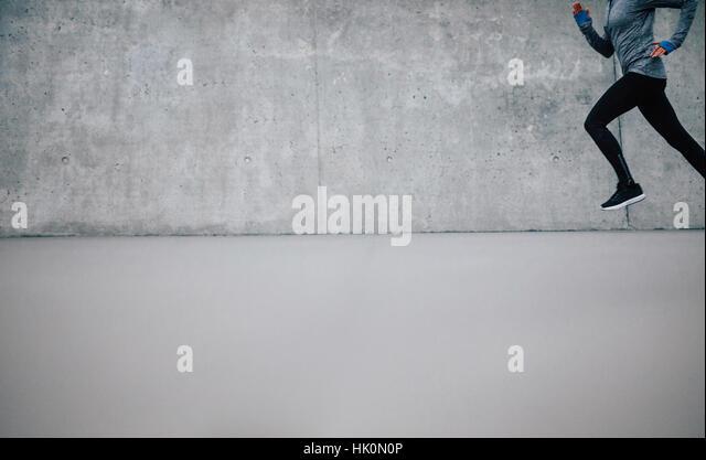 Läufer-Athlet läuft auf grauem Hintergrund. Fitness-Frau mit vielen textfreiraum Joggen. Stockbild