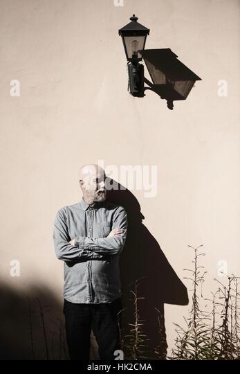 Ernsthafte und cool Alter Mann stand vor der Wand. Sonnenschein und schweren Schatten. Gebäudehülle mit Stockbild