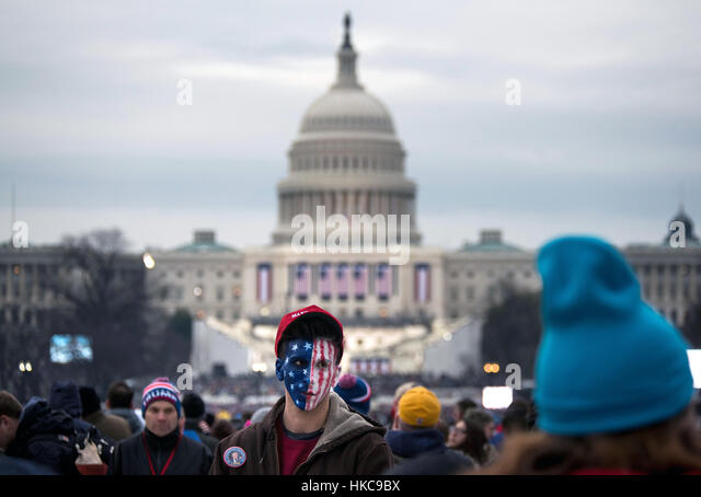 Ein Mann mit einer amerikanischen Flagge auf seinem Gesicht gemalt steht in der Menge auf der National Mall am Morgen Stockbild
