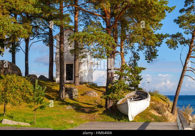 Felsige Küste der Ostsee mit weißen Boot, Fisher Holzhaus und Kiefern. Sonniger Tag. Stockbild