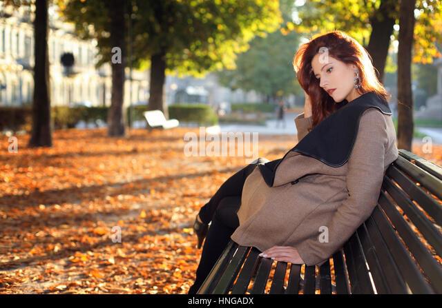 Schöne rote kurzhaarige Frau auf einer Bank im Stadtpark. Saisonale Schuss Stockbild