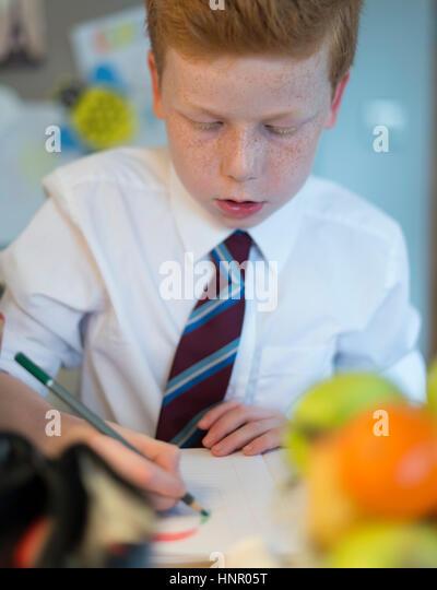 Ein Junge, zeichnen für die Hausaufgaben in seiner Küche zu Hause. Stockbild