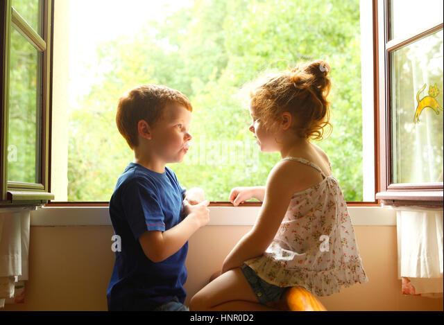 Bruder und Schwester miteinander zu reden, durch ein Fenster. Stockbild