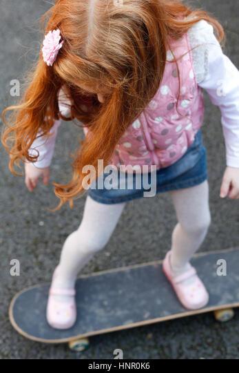 6 Jahre altes Mädchen mit roten Haaren auf dem skateboard Stockbild