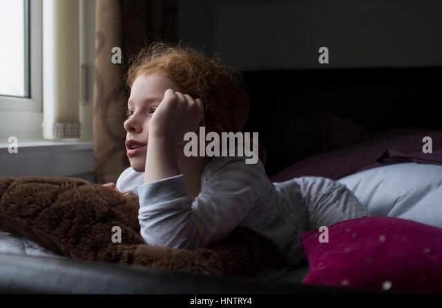 Ein kleines Mädchen auf ihrem Bett Stockbild