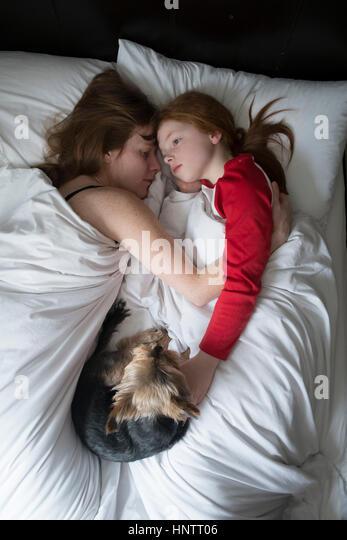Ein kleines Mädchen mit ihrer Mutter und Hund morgens im Bett. Stockbild