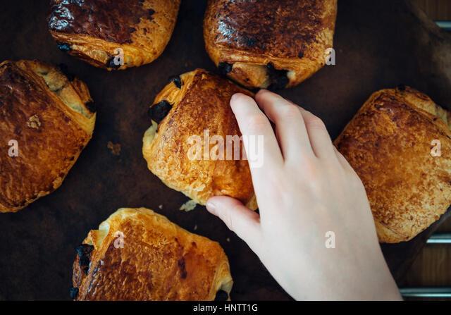 Eine Hand nimmt einen Gebäck Pain au chocolate Stockbild