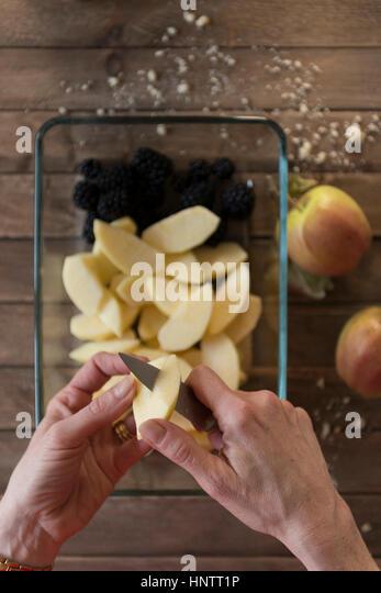 Eine Frau bereitet ein Fruchtpudding bröckeln. Schneiden Äpfel. Stockbild