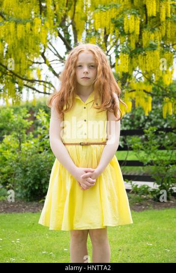 Ein kleines Mädchen im gelben Kleid stehen vor einem gelben Baum. Stockbild
