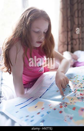 Ein kleines Mädchen Blick auf eine Karte in ihrem Schlafzimmer Stockbild