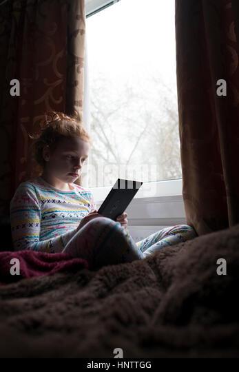Ein kleines Mädchen, das Lesen eines Buches auf einem Tablet. Stockbild