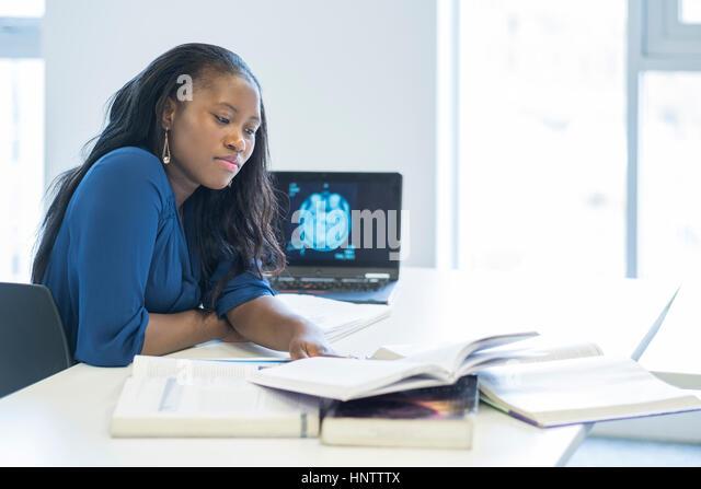 Ein weiblicher Studierender mit einem Laptop und Text Bücher. Stockbild