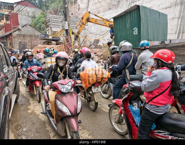 Menschen fahren Roller & Motorräder, tragen Helme & Schutzausrüstung, Stadtstraße, geparkt Stockbild