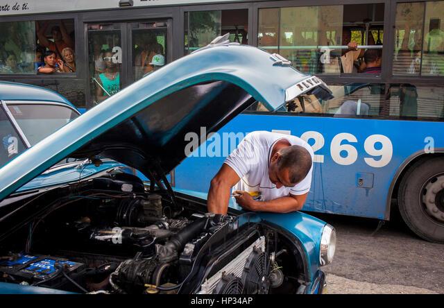 Öffentlicher Bus und Mann Reparatur Autos, Straßenszene in Dragones Straße, Centro Habana District, Stockbild