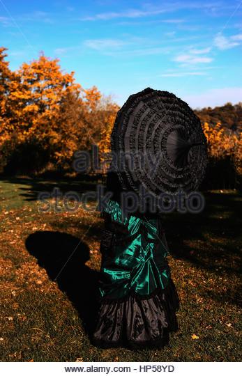 Rückansicht des viktorianischen Frau mit Regenschirm Stockbild