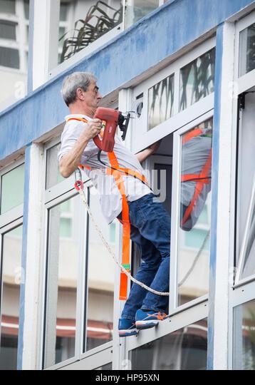 Mann mit Elektrowerkzeug balancieren prekär auf Fenstersims. Stockbild