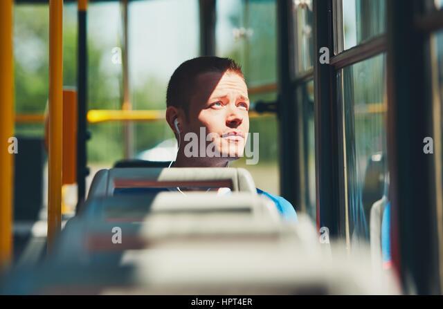Alltag und pendeln zur Arbeit mit öffentlichen Verkehrsmitteln. Hübscher junger Mann ist mit der Straßenbahn Stockbild